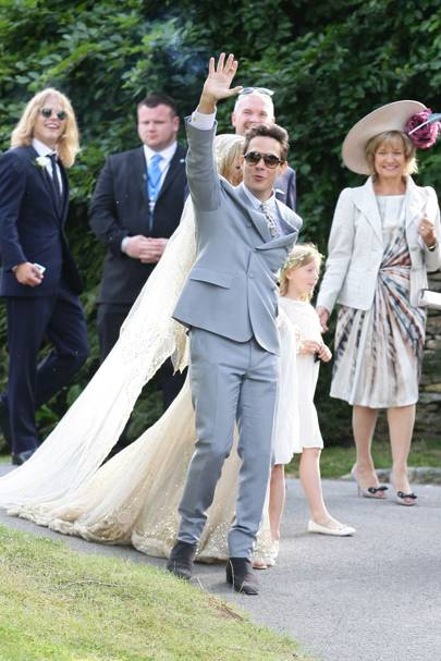 Jamie Hince and his new bride Kate Moss wave to waiting fans outside the church