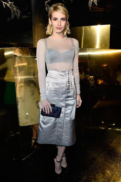 0349290e45d Emma took center stage at the same show wearing a metallic silver a-line  skirt. She styled the piece with a high-neck sheer top