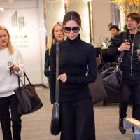 Victoria strutted through JFK airport looking typically chic in a simple  camel coat paired with white stilettos 937f0f8ceee