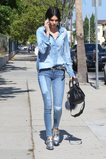 6487ac1de5 We love the patchwork detailing on Kendall Jenner s jeans. The model adds  an extra western touch to her double denim in the form of a cool studded  belt.
