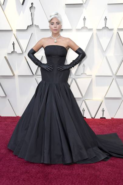 d13901aa0 Lady Gaga opted for a custom bustier dress in black silk faille by  Alexander McQueen, with engineered corset seaming and black leather gloves  at the 2019 ...
