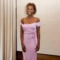 Rae wearing a lilac dress