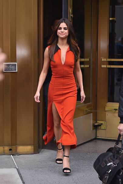 2b8bf819be5 The singer shows off her incredible figure in a sleeveless orange  Christopher Kane ensemble with a thigh-high slit that she pairs with a  black heel.